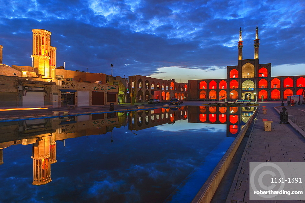 Amir Chaqmaq complex facade illuminated at sunrise and reflecting in a pond, Yzad, Yazd province, Iran