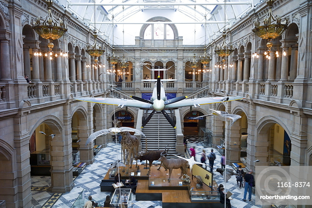 Visitors at Kelvingrove Art Gallery and Museum with suspended Spitfire World War II airplane exhibit on display in the West Court in Glasgow, Scotland, United Kingdom, Europe