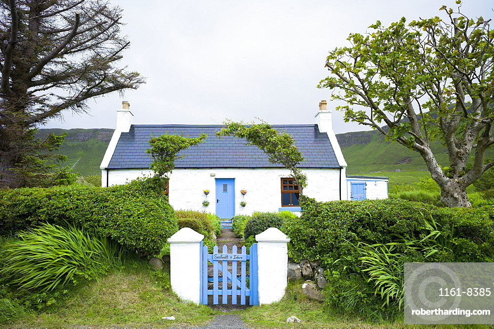 Quaint traditional Highland cottage in patriotic blue and white colours to match Scottish flag, near Linicro in the Highlands of Scotland, United Kingodm, Europe