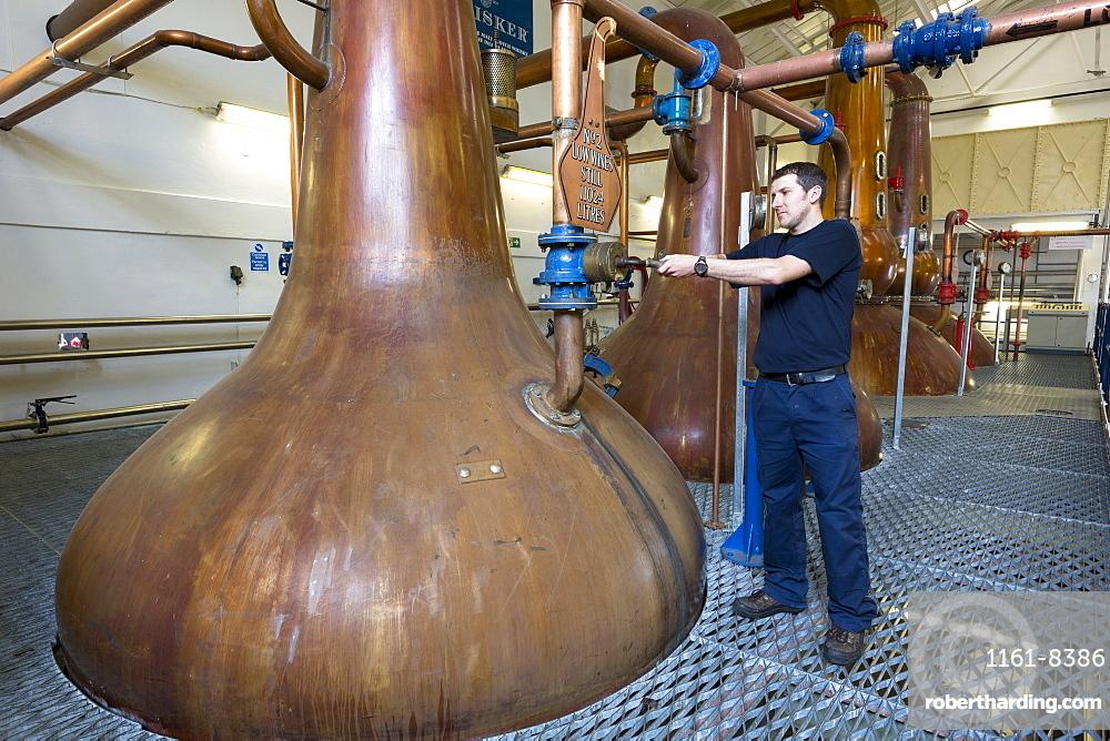 Stillsman inspecting copper spirit stills in the Stillshouse at Talisker Whisky Distillery making single malt whisky in Carbost on Isle of Skye, Scotland, United Kingodm, Europe