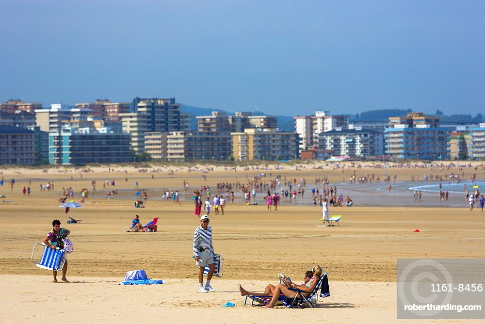 Beach scene and people sunbathing on summer holiday in Laredo, Cantabria, Spain, Europe