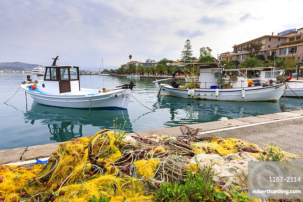 Colourful fishing nets on quay, boats, man mending nets, waterfront, Nafplio (Nafplion), Argolic Gulf, Peloponnese, Greece, Europe
