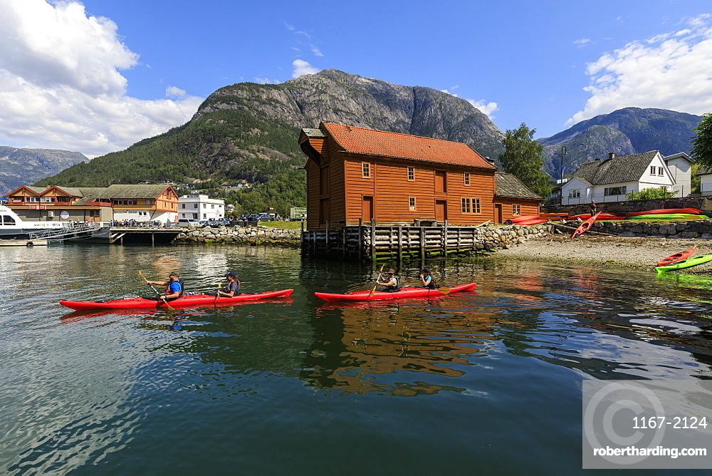 Sea kayakers head off, beautiful Eidfjord village, mountains and beach, sunny day, Norwegian Western Fjords, Norway, Scandinavia, Europe