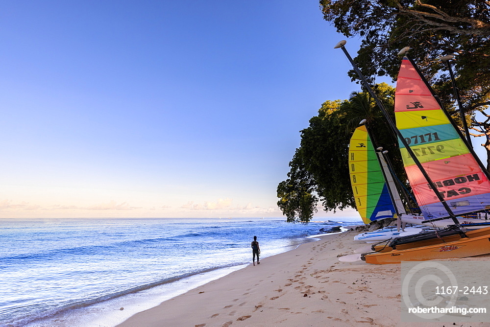 Paynes Bay at sunrise, lady exercises on beach, colourful sail boats, beautiful West Coast, Barbados, Windward Islands, West Indies, Caribbean, Central America