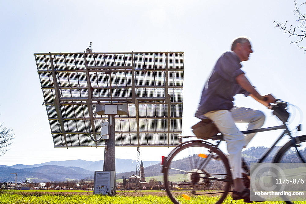 View of cyclist and solar module along Soitec Landscape, St. Georgen, Freiburg, Germany