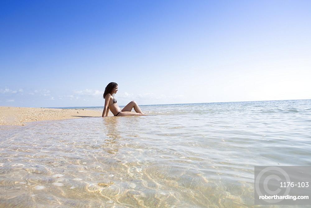 A young woman on a beach near Trancoso and Porto Seguro, Bahia, Brazil, South America
