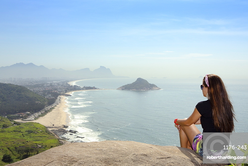 A young hiker looking out from the viewpoint over Pontal and Recreio dos Bandeirantes beaches in Barra da Tijuca, Rio de Janeiro, Brazil, South America