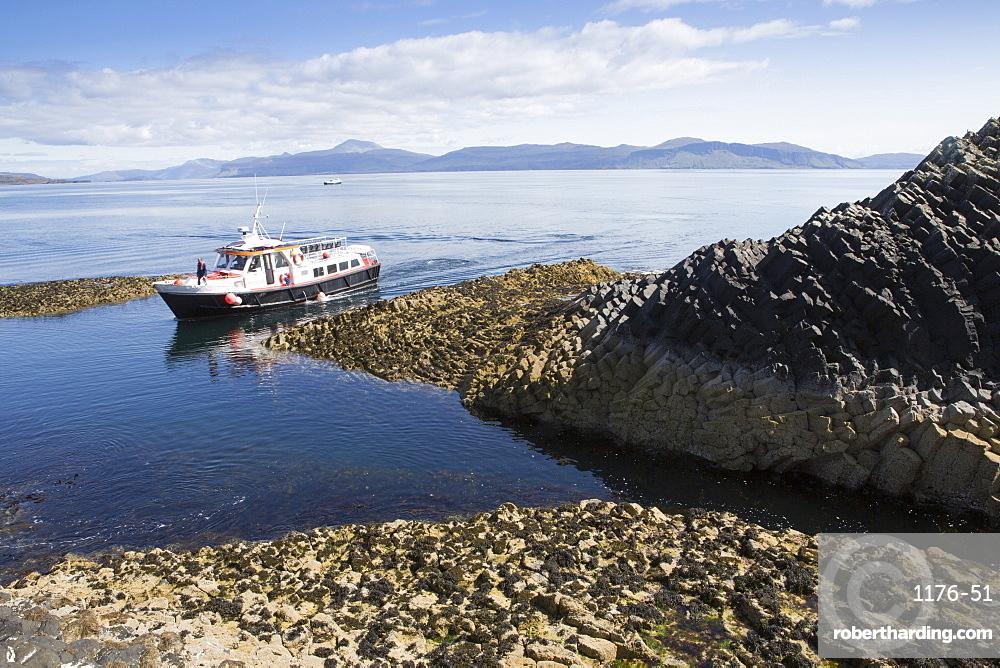 Basalt columns and a tourist ferry, Staffa Island, Inner Hebrides, Scotland, United Kingdom, Euorpe