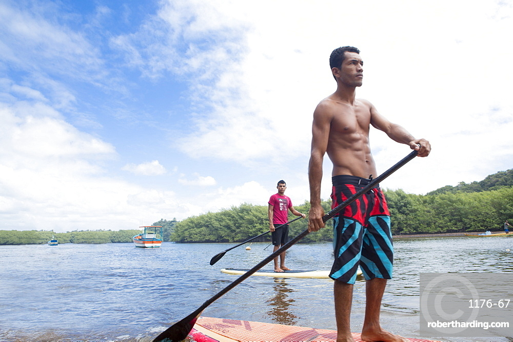 Locals riding stand-up surf boards, Caraiva River. Bahia, Brazil, South America