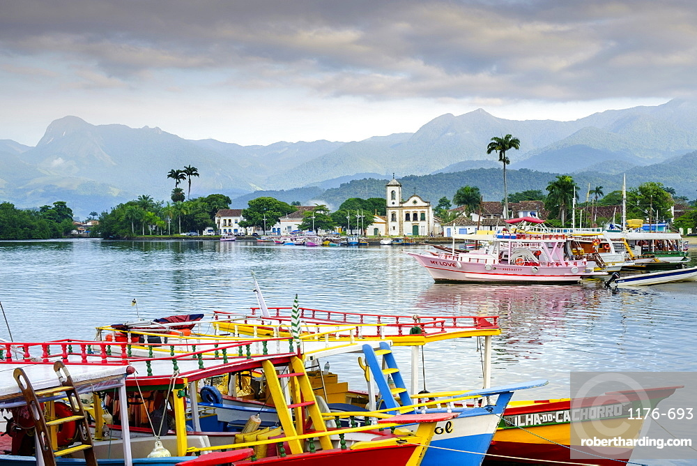 Fishing boats in Paraty village with the mountains of the Serra da Bocaina behind, Rio de Janeiro state, Brazil, South America