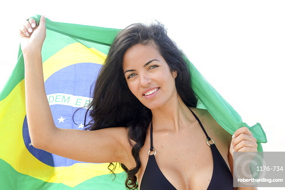 Young Brazilian woman, 20 to 29 years old, holding the Brazilian flag on a beach in Rio de Janeiro, Brazil, South America