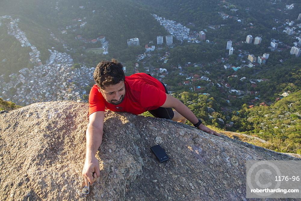 Climber on the top of the Morro dos Dois Irmaos (Two Brothers Hill) with Rocinha favela below, Rio de Janeiro, Brazil, South America