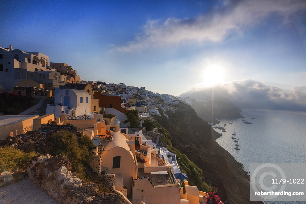 Sunbeam through the clouds over the Aegean Sea seen from the typical village of Oia, Santorini, Cyclades, Greek Islands, Greece, Europe