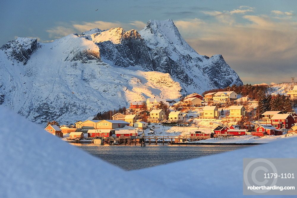 The last rays of sun on the fishing village and the snowy peaks, Kvalvika, Andoya, Reine, Nordland, Lofoten Islands, Arctic, Norway, Scandinavia, Europe