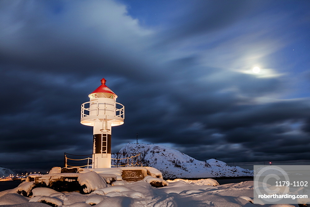 Lighthouse and full moon in the Arctic night with the village of Reine in the background, Nordland, Lofoten Islands, Arctic, Norway, Scandinavia, Europe