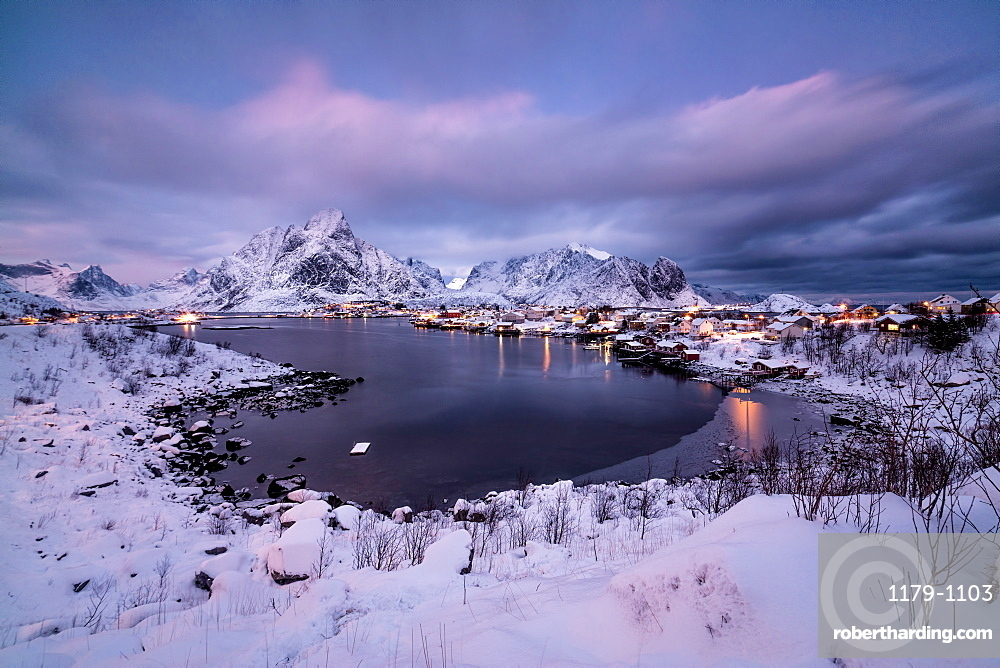 Colors of dawn on the fishing village surrounded by snowy peaks and frozen sea, Reine, Nordland, Lofoten Islands, Arctic, Norway, Scandinavia, Europe