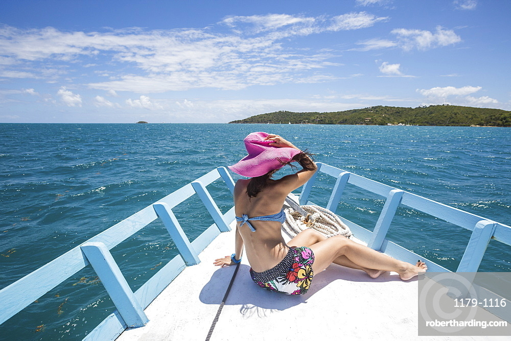 A tourist admires the colors of Caribbean Sea from a boat, Green Island, Antigua and Barbuda, Leeward Islands, West Indies, Caribbean, Central America