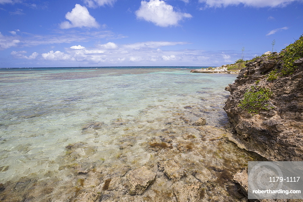 The turquoise shades of the Caribbean Sea seen from the cliffs of Green Island, Antigua and Barbuda, Leeward Islands, West Indies, Caribbean, Central America