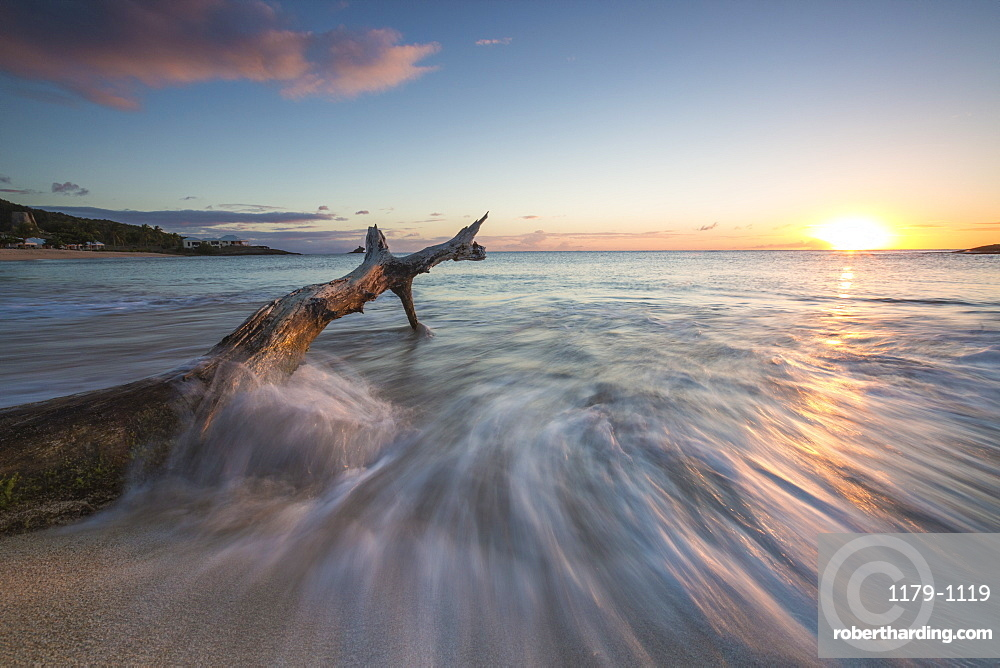 Waves on a tree trunk on the beach framed by the Caribbean sunset, Hawksbill Bay, Antigua, Antigua and Barbuda, Leeward Islands, West Indies, Caribbean, Central America