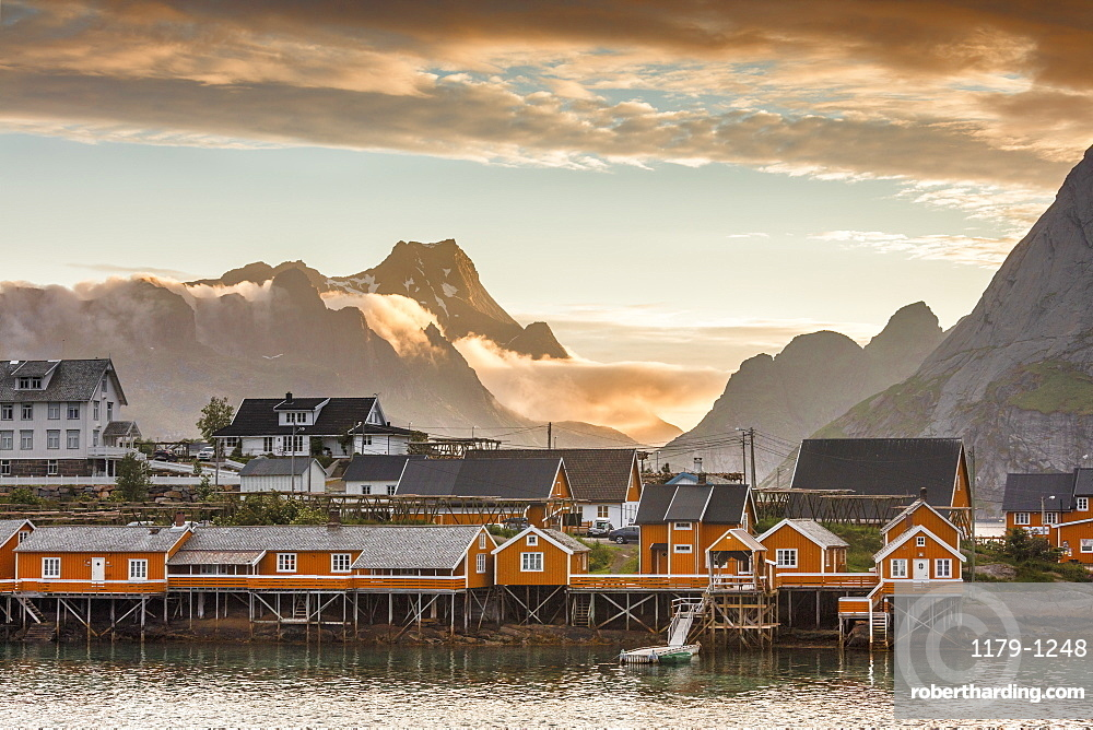 Sunset on the fishing village framed by rocky peaks and sea, Sakrisoya, Nordland county, Lofoten Islands, Arctic, Northern Norway, Scandinavia, Europe