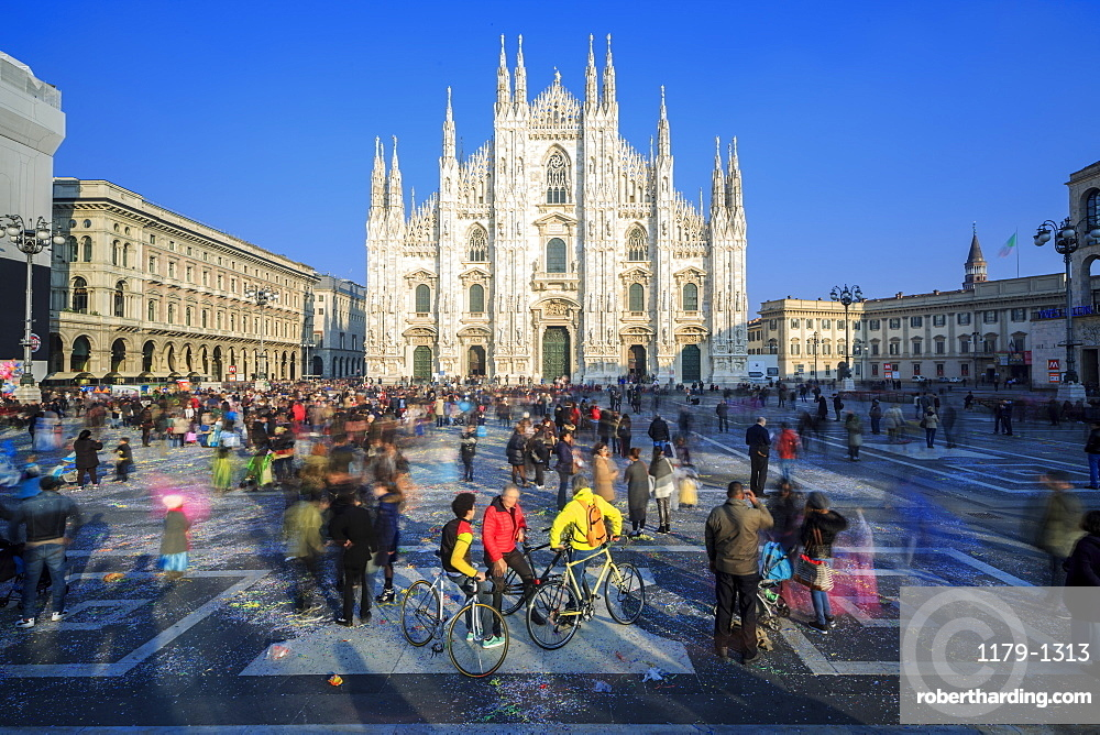 Cyclists in warm spring sun in front of the facade of the Gothic Duomo, Milan, Lombardy, Italy, Europe