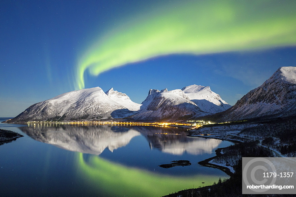 Northern lights (aurora borealis) and stars light up the snowy peaks reflected in the cold sea, Bergsbotn, Senja, Troms County, Norway, Scandinavia, Europe