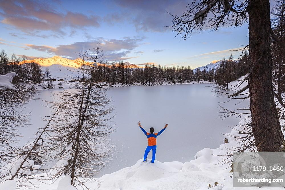 Hiker admires Lago Azzurro completely frozen at dawn, Spluga Valley, Province of Sondrio, Valtellina, Lombardy, Italy, Europe