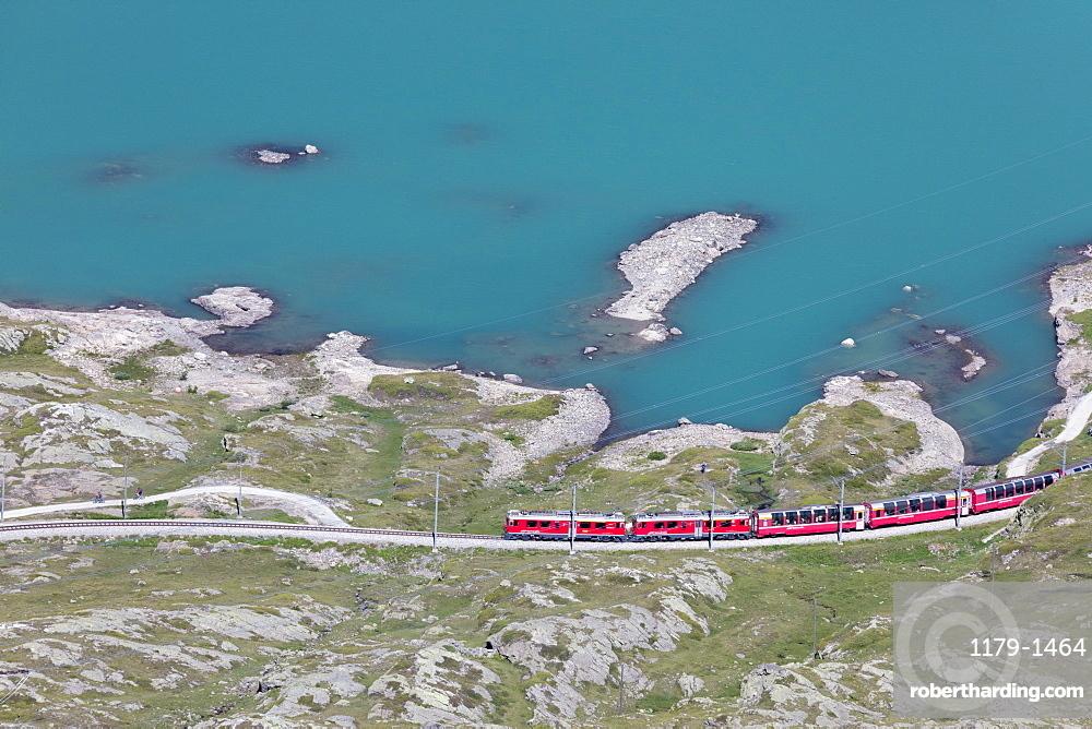 The Bernina Express train passes on the shores of Lago Bianco, Bernina Pass, Canton of Graubunden, Engadine, Switzerland, Europe