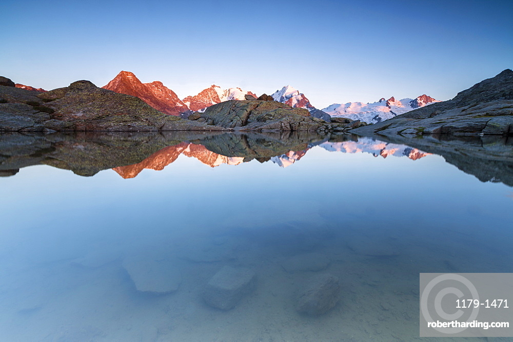 Snowy peaks reflected in the alpine lake at sunset, Fuorcla, Surlej, St. Moritz, Canton of Graubunden, Engadine, Switzerland, Europe