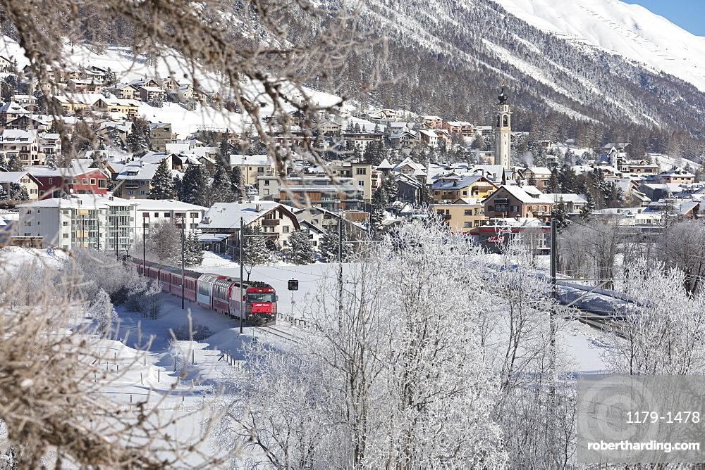 The red train runs across the snowy landscape around Samedan, Maloja, Canton of Graubunden, Engadine, Switzerland, Europe