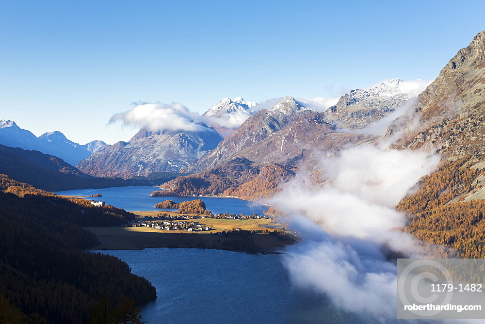 View of Sils and the blue lake surrounded by mist in autumn, Surlej, St. Moritz, Canton of Graubunden, Engadine, Switzerland, Europe