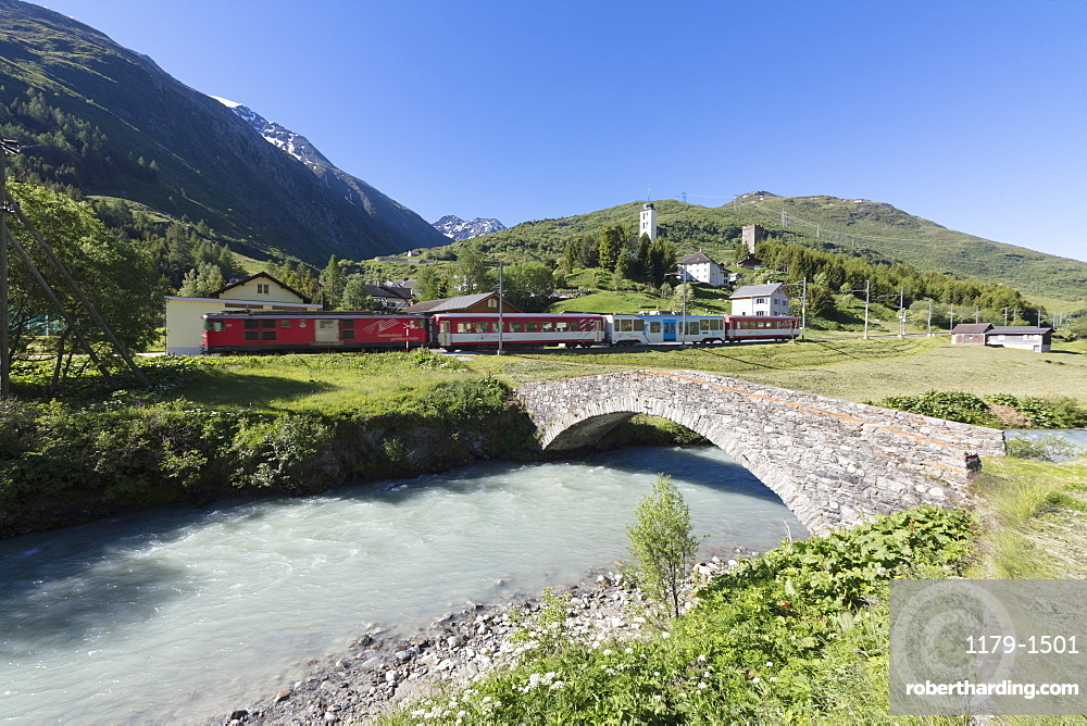 Typical red Swiss train on Hospental Viadukt surrounded by creek and green meadows, Andermatt, Canton of Uri, Switzerland, Europe