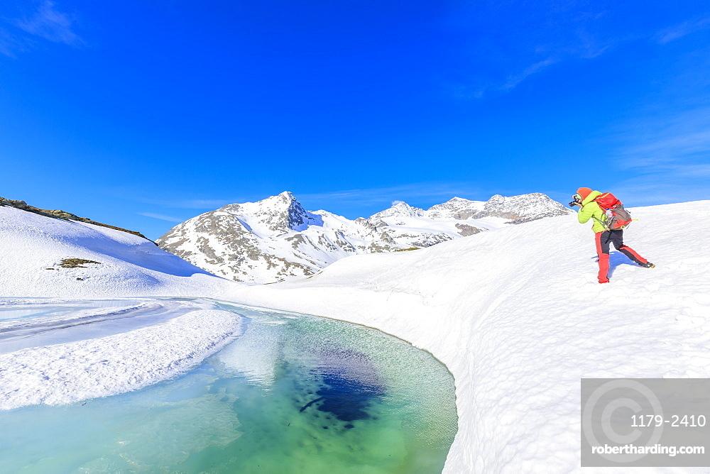 Photographer at the Bernina Pass during the spring thaw, St Moritz, Upper Engadine, Canton of Graubunden, Switzerland, Europe