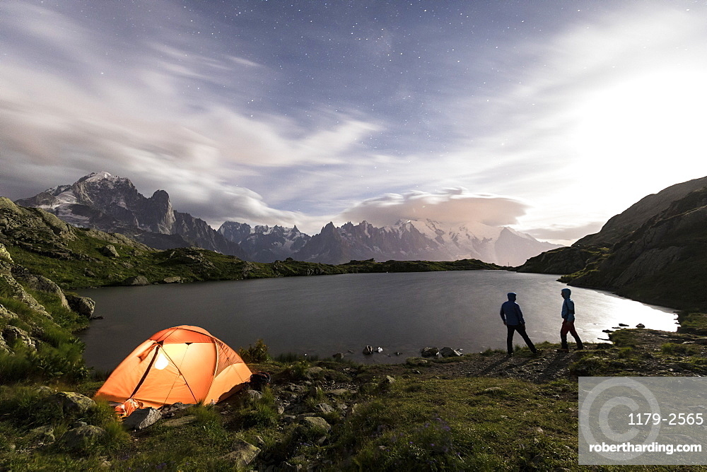 Hikers and tent on the shore of Lacs De Cheserys at night with Mont Blanc massif in the background, Chamonix, Haute Savoie, French Alps, France, Europe