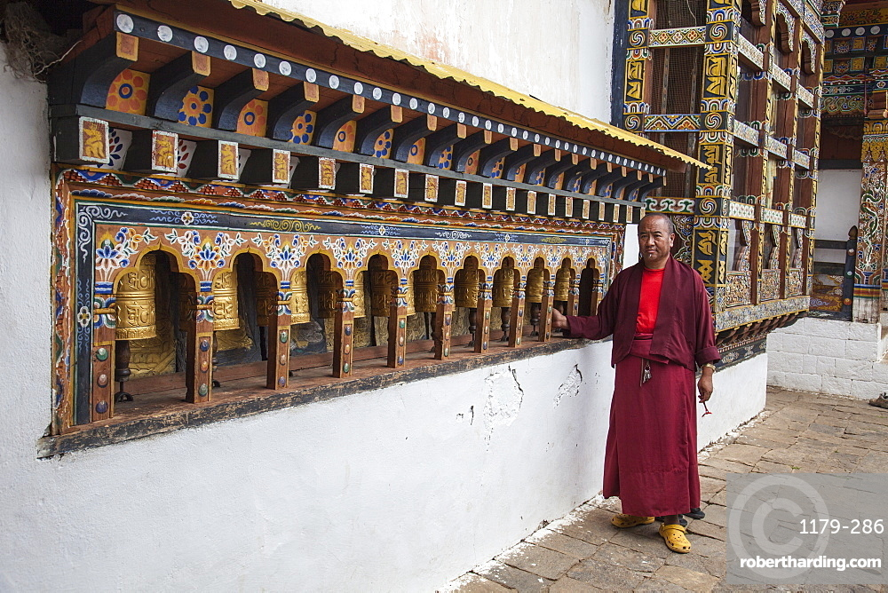 A monk rotates the roller-books of the Monastery of Punakha Dzong which are used to pray, Paro, Bhutan, Asia