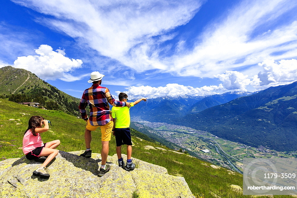 Father and children enjoy the view towards Morbegno from Alpe Bassetta, Lower Valtellina, Sondrio province, Lombardy, Italy, Europe