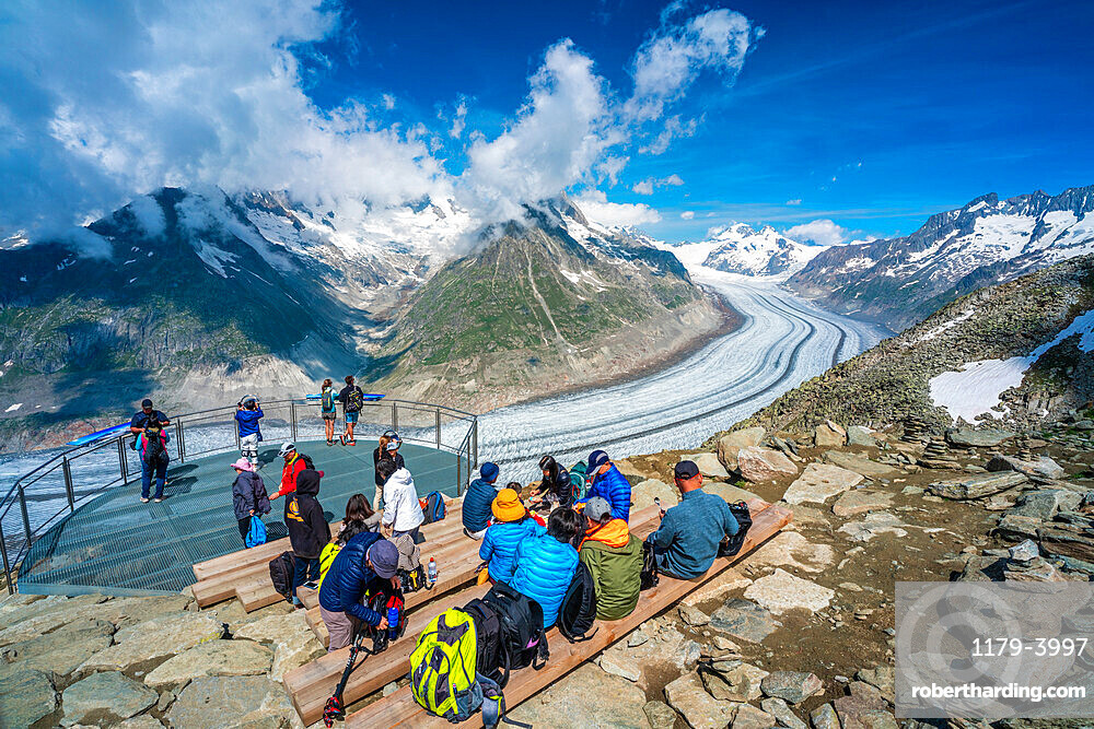 People admiring the majestic Aletsch Glacier from terrace at Eggishorn viewpoint, Bernese Alps, canton of Valais, Switzerland