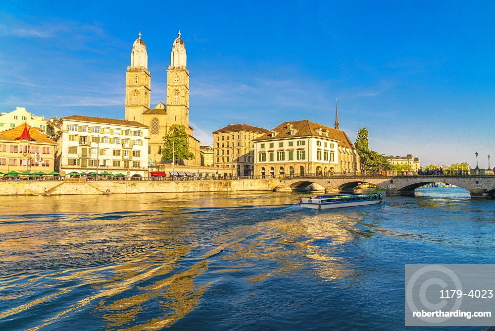 Ferry along Limmat River next to Munsterbrucke bridge with Grossmunster in background, Zurich, Switzerland