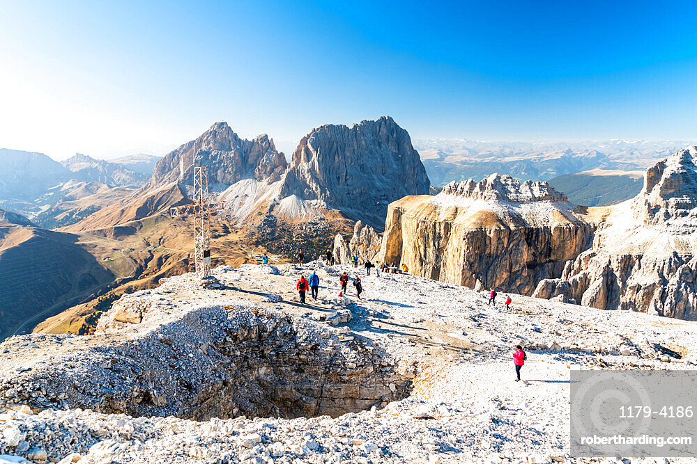 Hikers admiring Sella Pass, Sassolungo and Sassopiatto from top of Sass Pordoi, Dolomites, Trentino, Italy, Europe