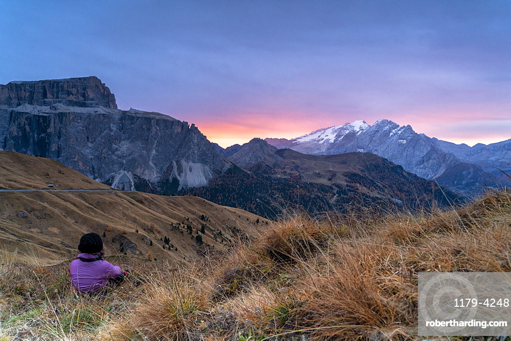 Rear view of woman sitting on grass admiring sunrise on Marmolada and Sass Pordoi, Passo Sella, Dolomites, South Tyrol, Italy