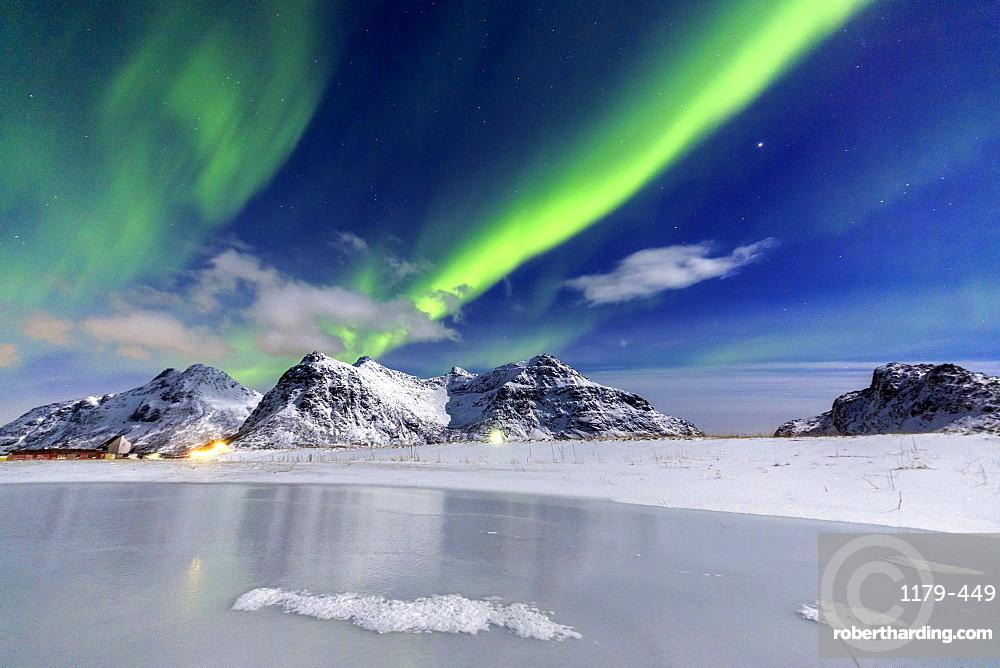 Northern Lights (aurora borealis) illuminate the sky and the snowy peaks, Flakstad, Lofoten Islands, Arctic, Norway, Scandinavia, Europe