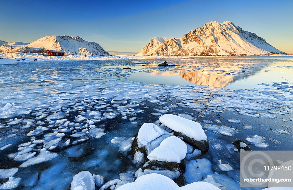 View of the mountains of Gymsoya (Gimsoya) from Smorten reflected in the clear partially frozen sea, Lofoten Islands, Arctic, Norway, Scandinavia, Europe
