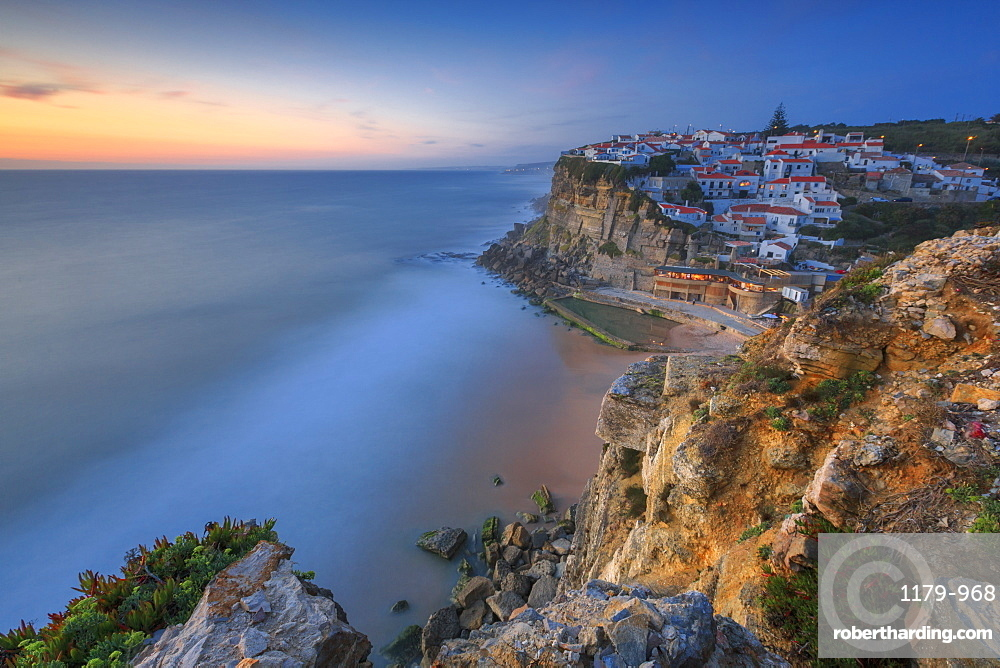 The soft colors of twilight frame the ocean and the village of Azenhas do Mar, Sintra, Portugal, Europe