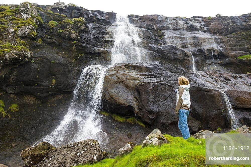Woman looking at a waterfall in Estuyroy, Faroe islands, Denmark