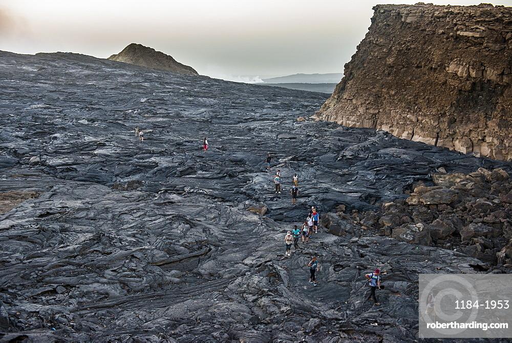 Tourists walking through lava field around the very active Erta Ale shield volcano, Danakil depression, Ethiopia, Africa
