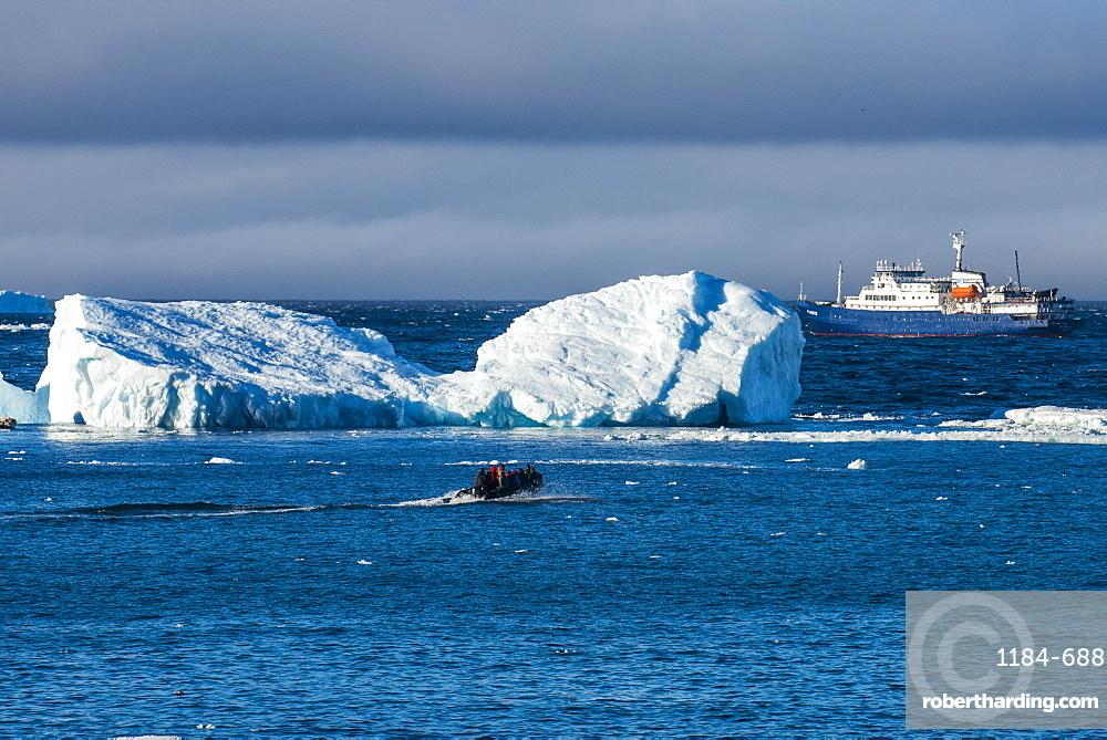 Zodiac cruising back to a cruise ship anchoring behind an iceberg, Brown Bluff, Antarctica, Polar Regions