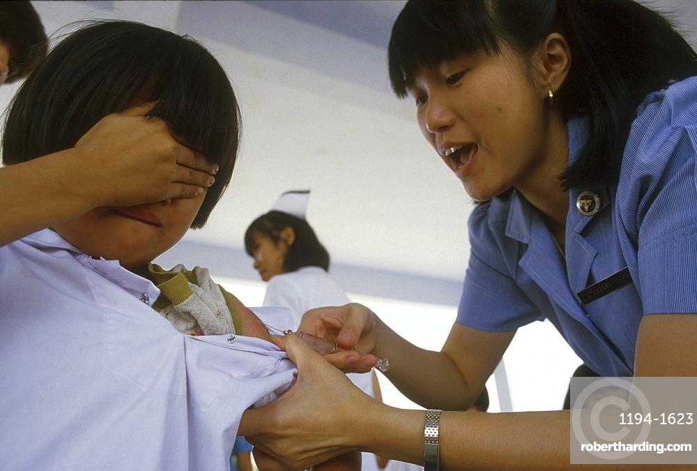 Thailand nurse giving a school an immunisation, chiang mai