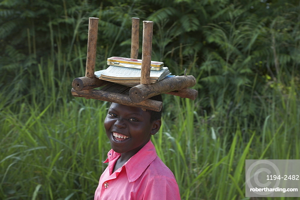 South sudan student of lutaya primary school walking to school with her books and stool to sit on as there is usually no furniture in the classrooms. yei