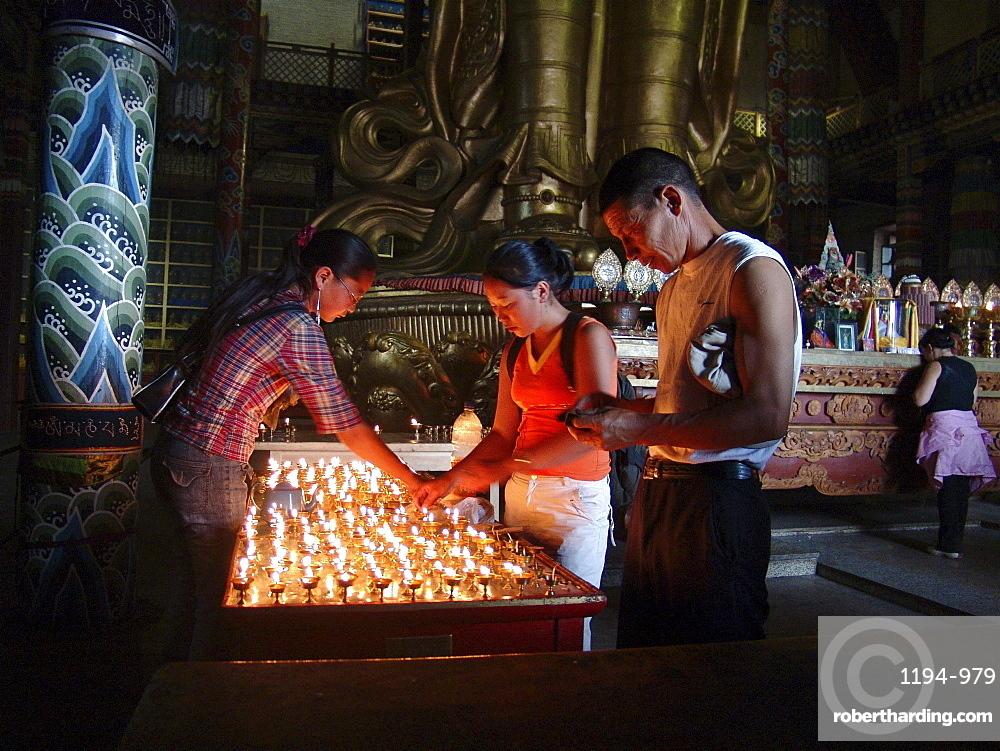 Mongolia ligthing candles inside migjid janraisig sum temple at gandan monastery, ulaan baatur