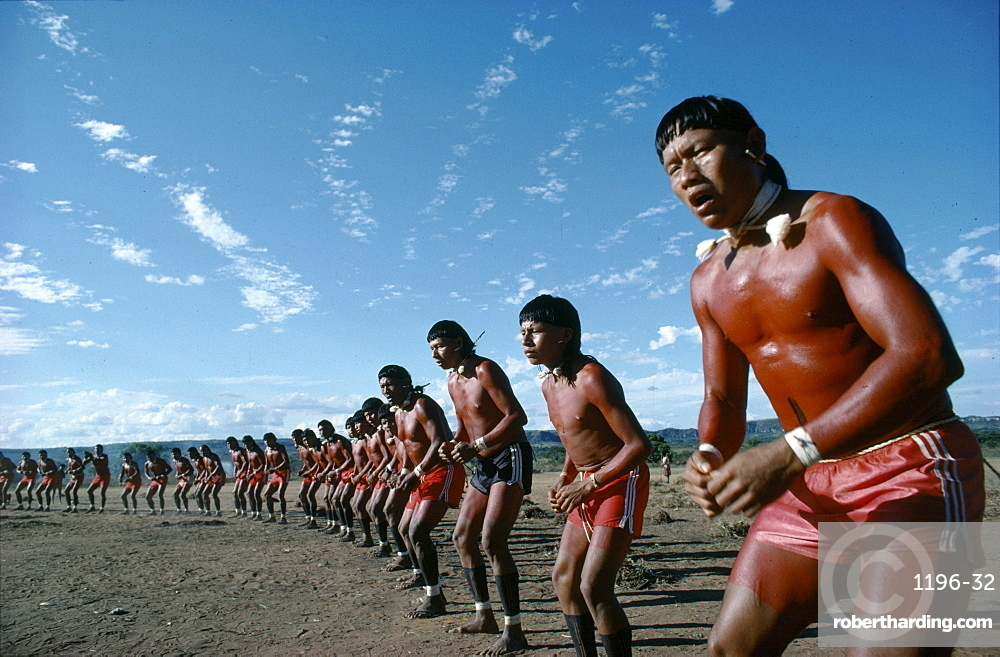 Xavante warriors prepare to wrestle wooden poles, a of taming or harnessing dark jungle forests. Brazil